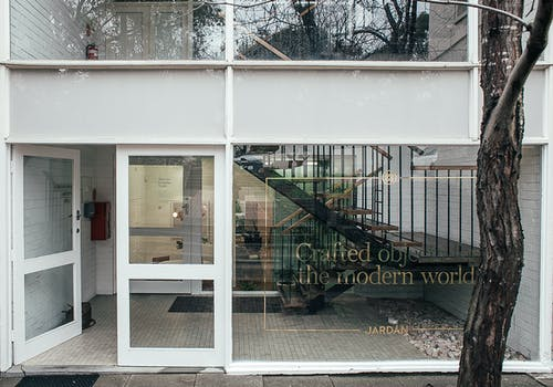 Modern building with inscription on windows and doorway and staircase located on street in city with tree trunk