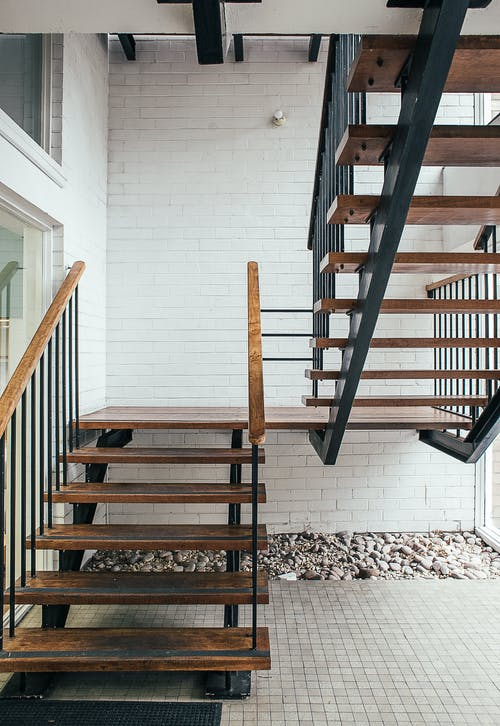 Brown Wooden Staircase on White and Black Floor Tiles