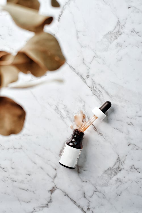 White and Black Bottle on White Textile