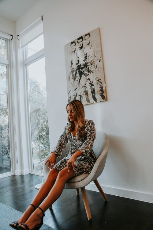 Stylish woman chilling in chair in bright hall