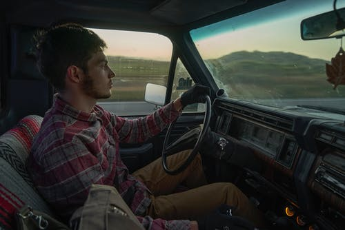 Man in Red Plaid Dress Shirt Driving Car