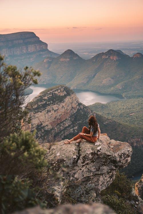 Woman in Brown Dress Sitting on Rock