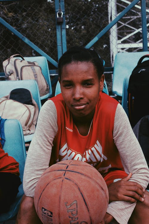 Black sportswoman sitting with ball