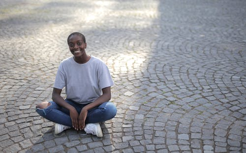 Man in White Crew Neck T-shirt and Blue Denim Jeans Sitting on Gray Concrete Pavement