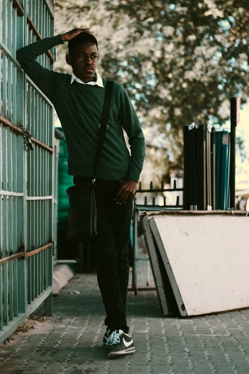 Worried black teen leaning on wall and thinking about trouble