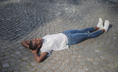 Man in White Shirt and Blue Denim Jeans Lying on Concrete Floor