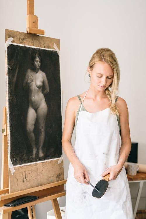 Mulher De Camiseta Branca Em Pé Ao Lado Da Pintura Em Moldura De Madeira Preta
