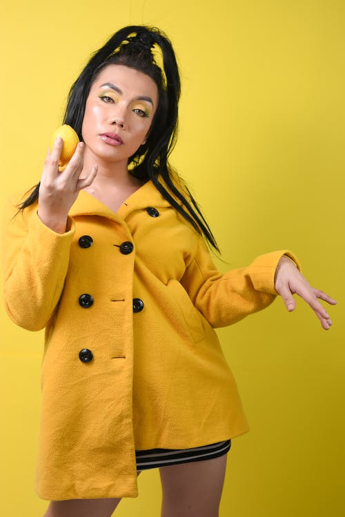 Woman in Yellow Coat Holding Apple