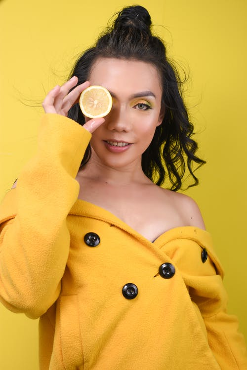 Woman in Yellow Coat Holding White Round Ornament