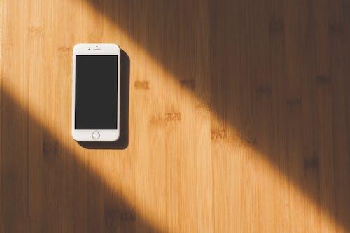 Бесплатное стоковое фото с iphone, белый, деревянный стол, мобильный