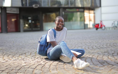 Woman in White Shirt and Blue Denim Jeans Sitting on Concrete Floor