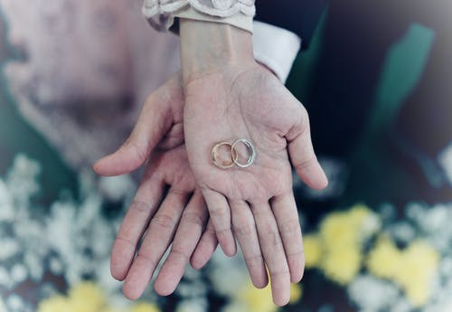 Person Holding Wedding Rings
