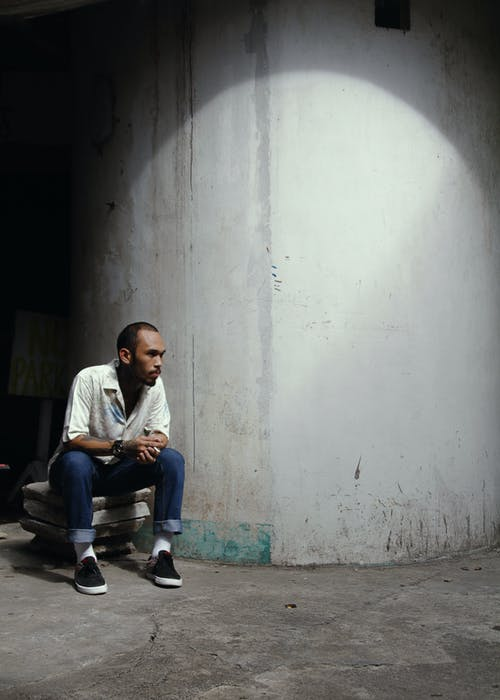 Serious ethnic male with short brown hair in white shirt and jeans sitting near old white concrete wall