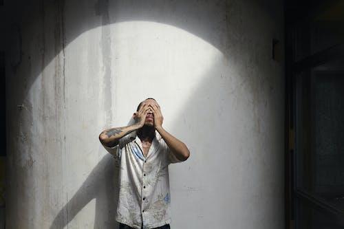 Homme En Vêtements Décontractés Fermant Les Yeux Avec Les Mains