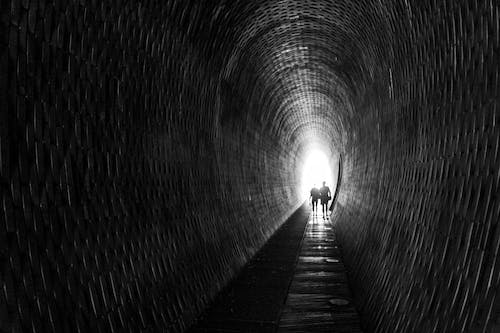 Black and white of anonymous people strolling along narrow empty tunnel with light behind back