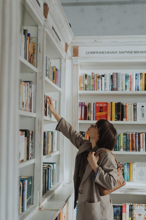 Woman in Beige Coat Standing in Front of White Wooden Book Shelf