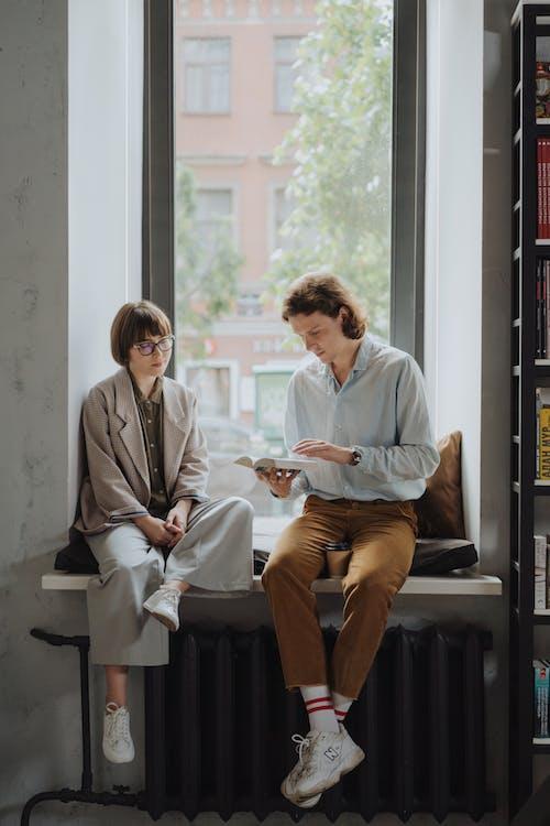 Man in Blue Dress Shirt Sitting Beside Woman in Gray Blazer