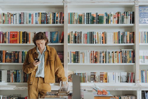 Woman in Brown Coat Sitting on Chair in Front of Books