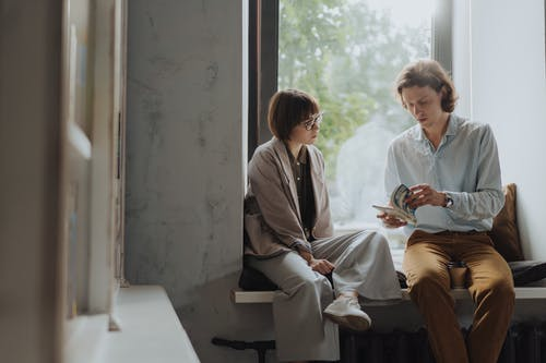 Man and Woman Sitting on Chair Beside Window