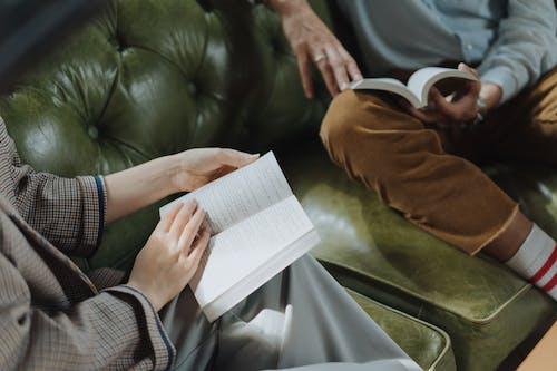 Persona In Maglione Marrone Che Tiene Libro Bianco