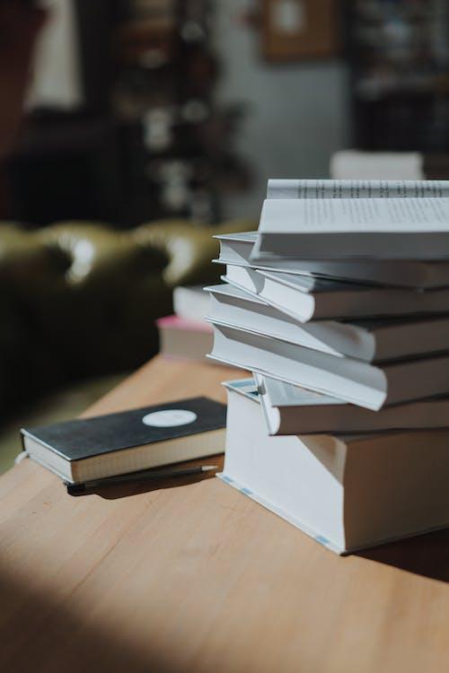 茶色の木製テーブルの白と茶色の本