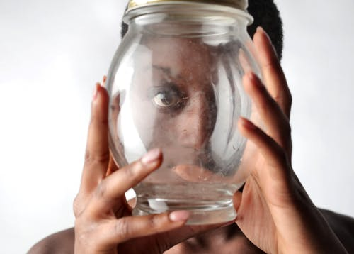 Person Holding Clear Glass Jar