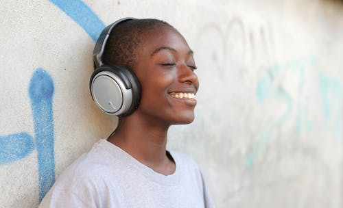 Smiling Woman in Gray Crew Neck Shirt Wearing Black and Silver Headphones