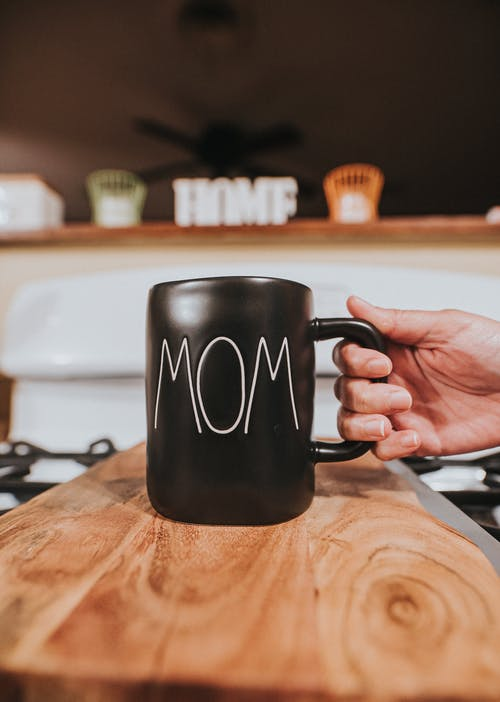 Crop anonymous person taking black ceramic mug with white word Mom placed on wooden table in living room