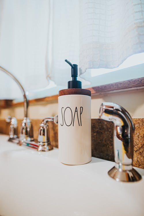 Ceramic soap dispenser placed on wash basin