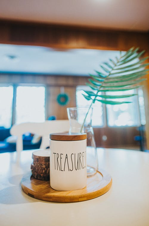 Composition of ceramic jar with word Treasures on dining table