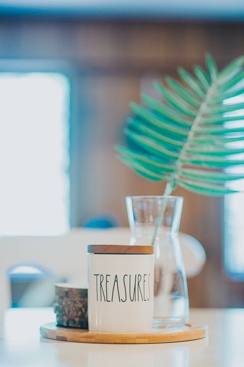 Composition of white ceramic sugar bowl with word Treasures placed on wooden board near green plant twig in glass vase on dining table