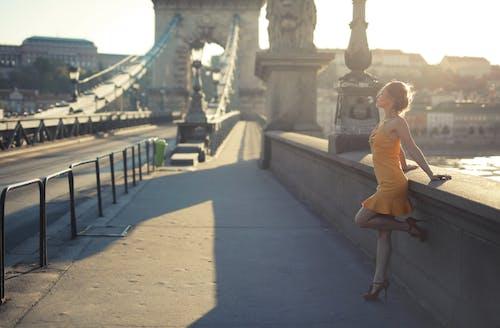 Woman in Brown Dress Walking on Sidewalk