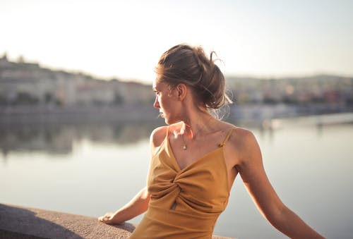 Woman in Orange Spaghetti Strap Top Sitting on Concrete Wall
