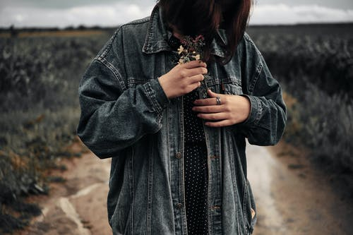 Woman in Blue Denim Jacket Holding Red and Yellow Flower