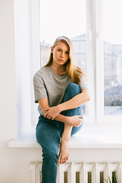 Woman in Gray Long Sleeve Shirt and Blue Denim Jeans Sitting on Window