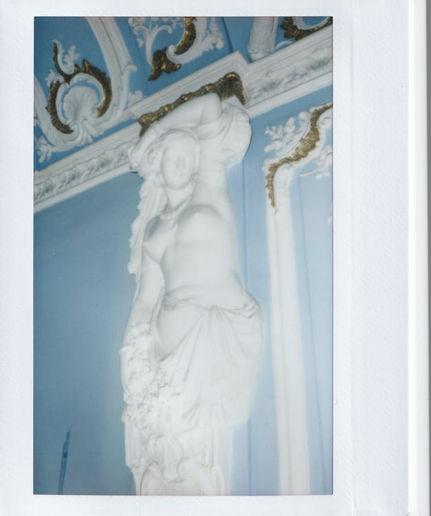 Low angle of white sculpture of nude female from stone in interior of old building