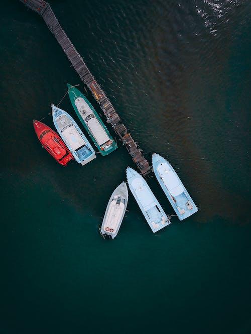 Yachts moored in ocean near wooden dock