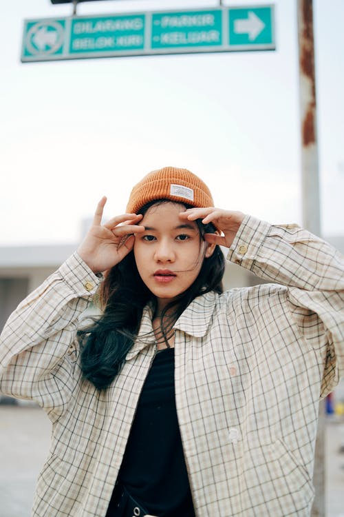 Woman in Beige and Black Plaid Coat and Orange Knit Cap