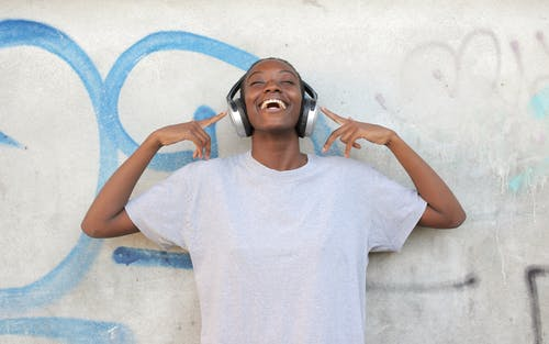Woman in White Crew Neck T-shirt Wearing Headphones