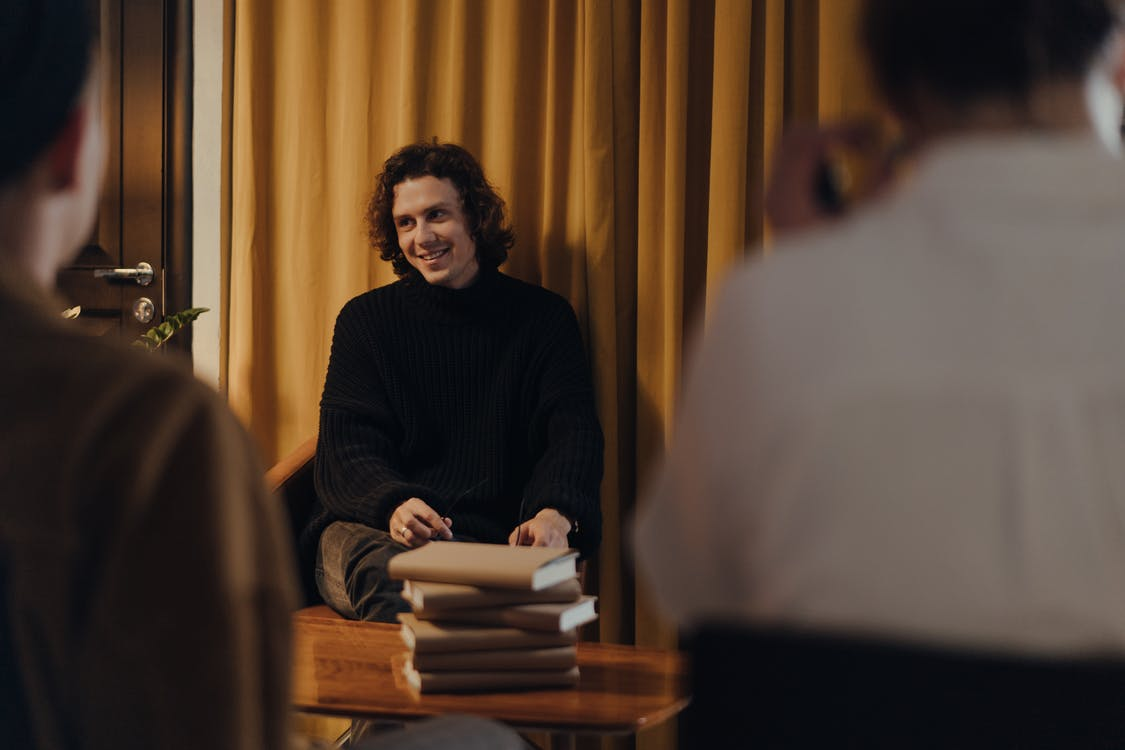Hombre De Suéter Negro Sentado En Una Silla