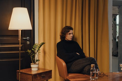 Man in Black Crew Neck T-shirt Sitting on Brown Sofa Chair