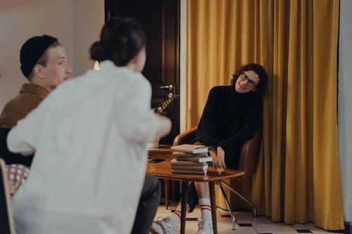 Hombre En Camiseta Negra Con Cuello Redondo Sentado Al Lado De Una Mujer En Camisa Blanca De Manga Larga