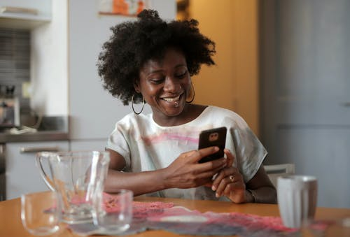 Woman in White Crew Neck T-shirt Holding Black Smartphone