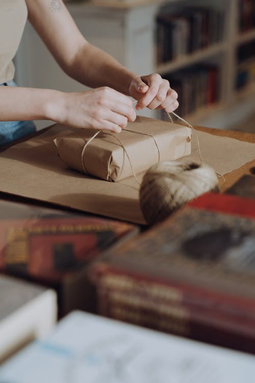 Person Holding Brown Yarn on Brown Wooden Table