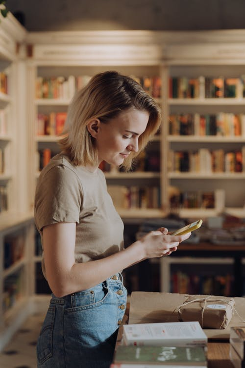Woman in White T-shirt and Blue Denim Shorts Holding Smartphone