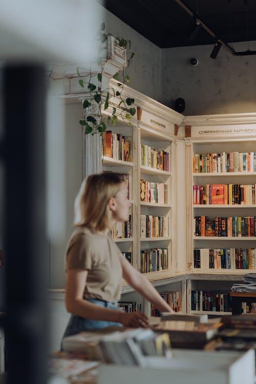 Girl in White T-shirt Standing Beside Brown Wooden Book Shelf