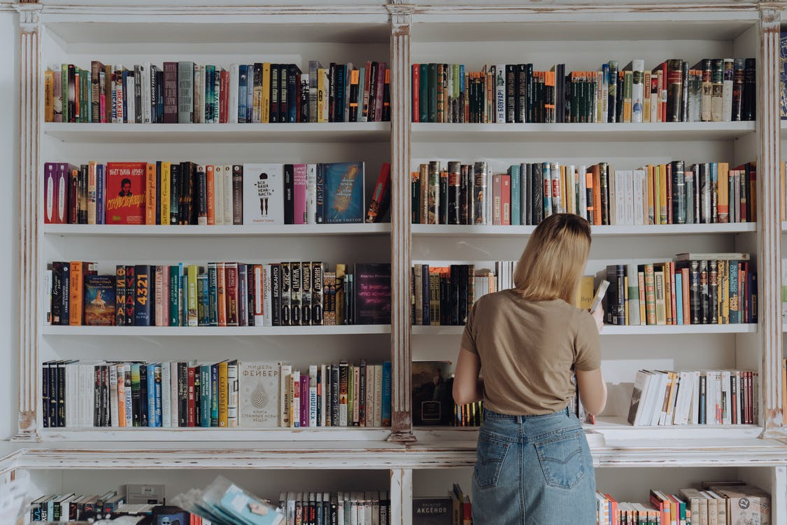 Woman in Beige Shirt and Blue Denim Jeans Standing in Front of Books
