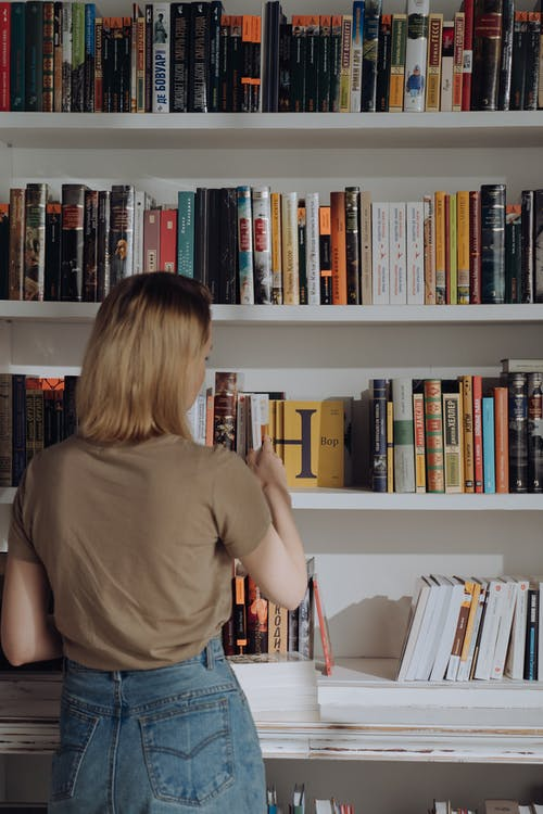 Boy in Brown T-shirt Standing in Front of Books