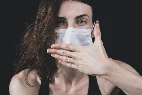 Woman in Black Tank Top Covering Face With White Paper
