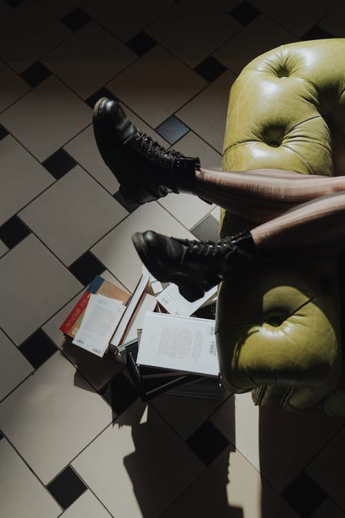 Person in Black Leather Boots Sitting on Yellow Leather Chair